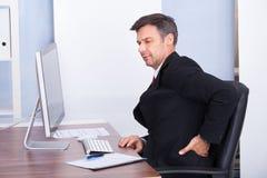Homem de negócios que sofre da dor nas costas fotografia de stock