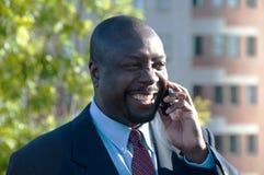 Homem de negócios que sorri & que fala no telefone de pilha Fotografia de Stock Royalty Free