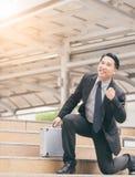 Homem de negócios que sorri e que aumenta seu punho no ar, no sucesso comercial, na realização, e nos conceitos da vitória fotografia de stock