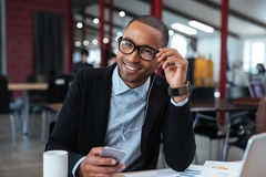 Homem de negócios que sorri e que toca em seus vidros Imagem de Stock Royalty Free