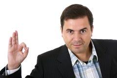 Homem de negócios que sorri fazendo o sinal aprovado Fotografia de Stock Royalty Free