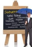 Homem de negócios que sorri na câmera e que guarda o guarda-chuva azul Imagem de Stock Royalty Free