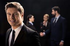 Homem de negócios que sorri no primeiro plano quando executivos que conectam atrás Fotos de Stock Royalty Free