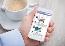 Homem de negócios que surfa o local social dos trabalhos em rede no telefone celular Imagem de Stock