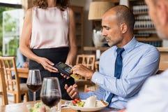 Homem de negócios que swiping o cartão de crédito fotografia de stock
