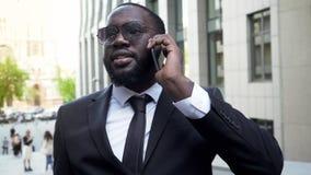 Homem de negócios que tem a conversação sobre o telefone celular, conversa com sócios, pessoa ávida de dinheiro foto de stock royalty free