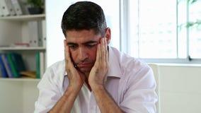Homem de negócios que tem uma dor de cabeça em sua mesa video estoque