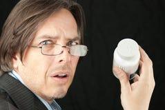 Homem de negócios que tenta ler o frasco de Pil Fotos de Stock