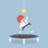 Homem de negócios que tenta travar a estrela saltando no trampolim ilustração royalty free