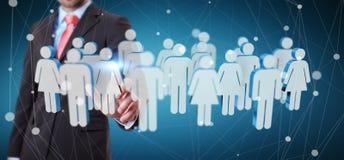 Homem de negócios que toca em 3D que rende o grupo de pessoas com seu finge Foto de Stock