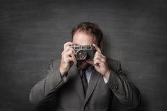 Homem de negócios que toma uma foto com a câmera velha do vintage imagem de stock