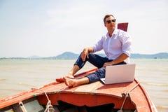 Homem de negócios que trabalha com computador em um barco, escritório exterior agradável fotografia de stock royalty free