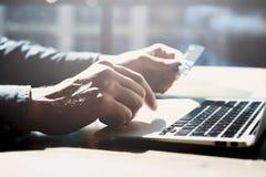Homem de negócios que trabalha com o caderno genérico do projeto Cartão plástico dos pagamentos em linha, teclado das mãos Fundo  Fotografia de Stock