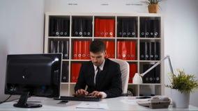 Homem de negócios que trabalha com o PC da tabela no escritório filme