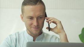 Homem de negócios que trabalha com o portátil que fala no telefone vídeos de arquivo