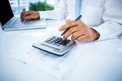 Homem de negócios que trabalha com portátil e calculadora Fotografia de Stock