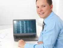 Homem de negócios que trabalha com seu portátil na mesa imagens de stock