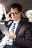 Homem de negócios que trabalha com tabuleta e o telefone esperto imagens de stock
