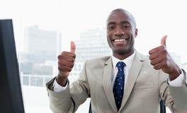 Homem de negócios que trabalha com um computador com os polegares acima foto de stock royalty free