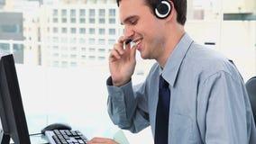 Homem de negócios que trabalha com um computador e uns auriculares Fotografia de Stock Royalty Free
