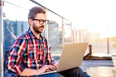 Homem de negócios que trabalha da casa no portátil, sentando-se no balcão imagem de stock