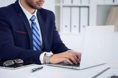 Homem de negócios que trabalha datilografando no laptop Equipe as mãos do ` s no caderno ou na pessoa do negócio no local de trab Foto de Stock