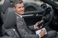 Homem de negócios que trabalha em seu carro fotografia de stock royalty free