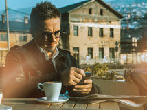 Homem de negócios que trabalha em um telefone celular e em um café bebendo Foto de Stock Royalty Free
