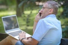 Homem de negócios que trabalha fora com caderno fotografia de stock royalty free