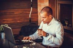 Homem de negócios que trabalha na linha com um portátil e que guarda um copo na fotos de stock
