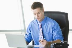 Homem de negócios que trabalha na mesa Imagens de Stock Royalty Free
