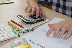 Homem de negócios que trabalha na mesa de escritório com calculadora Homem, mão do homem de negócios com a calculadora no escritó Imagens de Stock Royalty Free