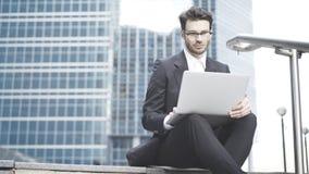 Homem de negócios que trabalha no ao ar livre com um portátil Imagens de Stock Royalty Free