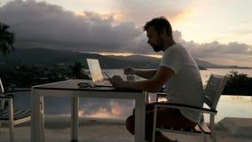 Homem de negócios que trabalha no caderno no terraço exterior com vista no mar da noite filme