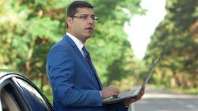 Homem de negócios que trabalha no computador ao lado do carro vídeos de arquivo