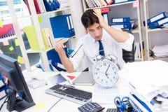 Homem de negócios que trabalha no escritório com as pilhas dos livros e dos papéis imagem de stock royalty free