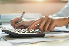 homem de negócios que trabalha no escritório da mesa com utilização de uma calculadora, aleta foto de stock