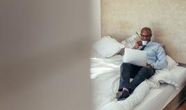 Homem de negócios que trabalha no laptop que encontra-se na cama imagem de stock