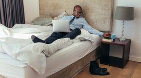 Homem de negócios que trabalha no laptop que encontra-se na cama fotos de stock