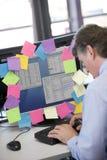 Homem de negócios que trabalha no PC coberto nos lembretes Imagem de Stock