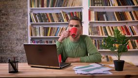 Homem de negócios que trabalha no portátil, café bebendo e tentando concentrar-se no escritório Bibliotecas no fundo video estoque