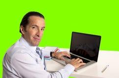 Homem de negócios que trabalha no portátil do computador que senta-se na chave do croma da mesa de escritório Fotos de Stock Royalty Free