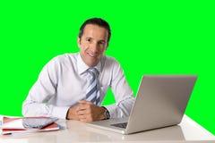 Homem de negócios que trabalha no portátil do computador que senta-se na chave do croma da mesa de escritório Fotografia de Stock Royalty Free
