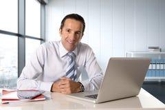 Homem de negócios que trabalha no portátil do computador que senta-se na mesa que olha segura Fotografia de Stock