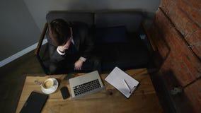 Homem de negócios que trabalha no portátil e no café bebendo no café o homem de negócios triste quer pendurar em um laço Vista su filme