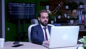 Homem de negócios que trabalha por muito tempo após as horas de fechamento do escritório vídeos de arquivo
