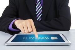 Homem de negócios que usa as janelas 10 na tabuleta Fotos de Stock Royalty Free
