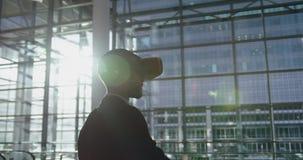 Homem de negócios que usa auriculares da realidade virtual na entrada no escritório 4k video estoque