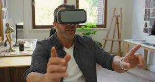 Homem de negócios que usa auriculares da realidade virtual na mesa 4k vídeos de arquivo