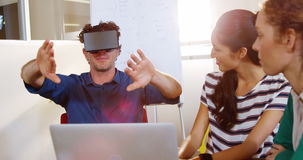 Homem de negócios que usa auriculares da realidade virtual na reunião
